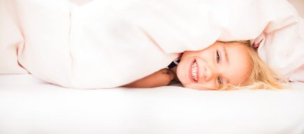 Smiling girl peeking under blanket